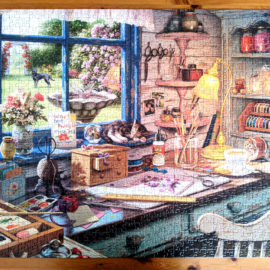 The Craft Shed shows the interior of a quaint shed packed with crafting supplies and tools with lovely view of a garden.
